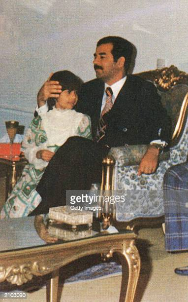 In this undated photo Saddam Hussein holds his daughter Hala