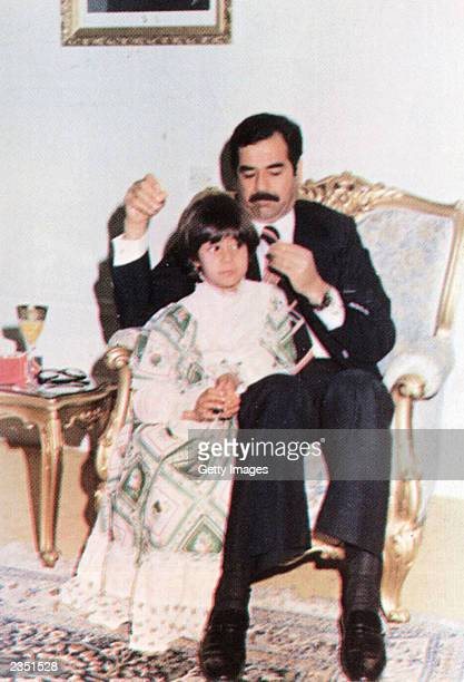 In this undated photo Saddam Hussein holds his daughter Rana Raghad Saddam Hussein and Rana Saddam Hussein daughters of Saddam Hussein and their nine...