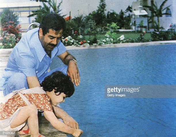 In this undated photo Saddam Hussein plays with his daughter Hala at a swimming pool