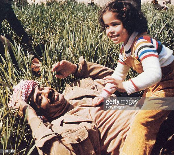 In this undated photo Saddam Hussein plays with his daughter Hala