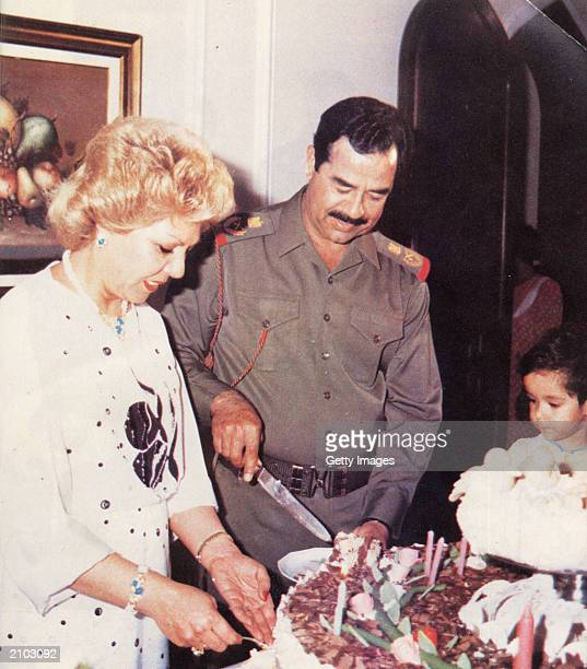 In this undated photo Saddam Hussein slices food with his first wife Sajida and his daughter Hala
