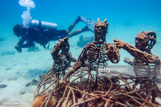 In this underwater photo taken on August 19, 2020 a diver swims next to metal figures set up on an artificial reef for marine conservation by Koh Tao...