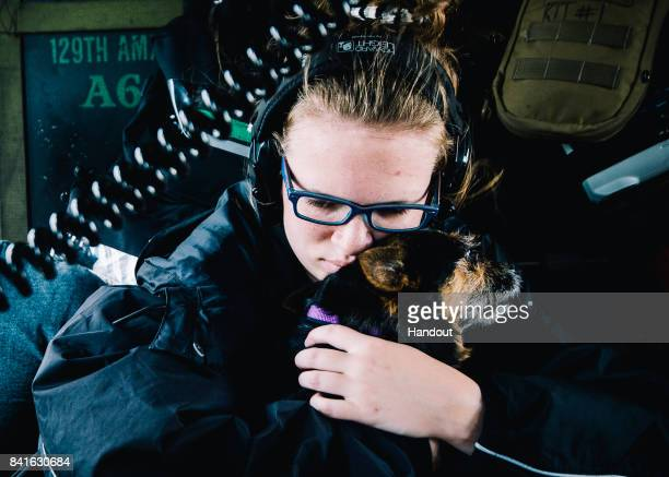 In this US Air Force handout A young girl clutches her dog after getting into an HH60 Pavehawk from the 129th Rescue Squadron for extraction to a...