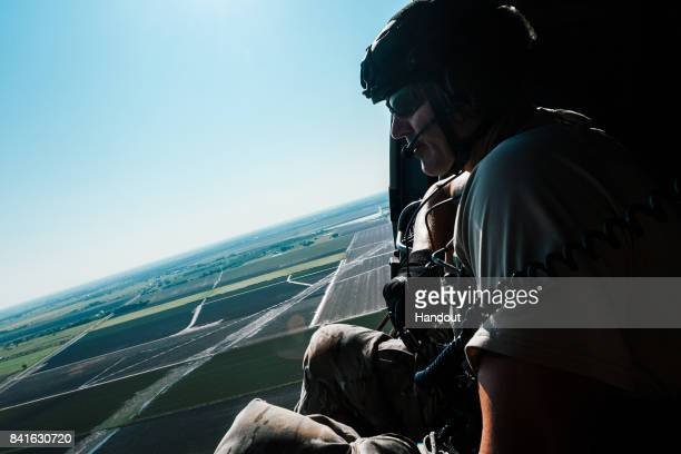 In this US Air Force handout Chief Master Sgt Eric Burke 131st Rescue Squadron pararescueman looks out the side door of a HH60 Pavehawk from the...