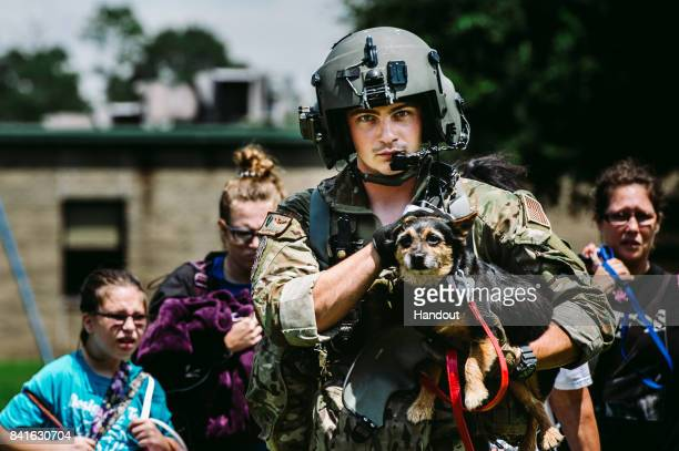 In this U.S. Air Force handout, Senior Airman Austin Hellweg, 129th Rescue Squadron special missions aviator, carries a dog and leads a family into...