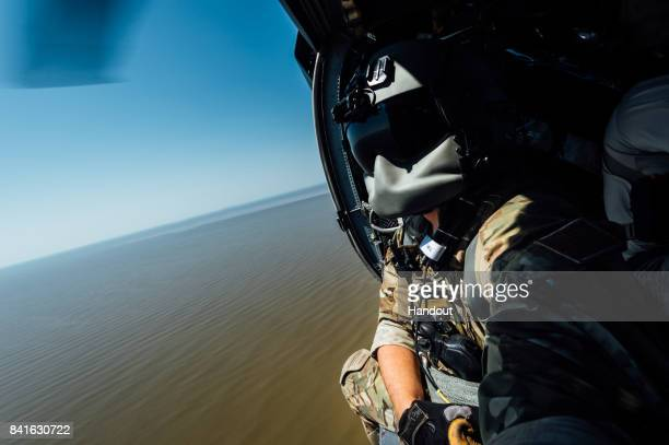 In this US Air Force handout Senior Airman Austin Hellweg 129th Rescue Squadron special missions aviator looks out the side door of a HH60 Pavehawk...
