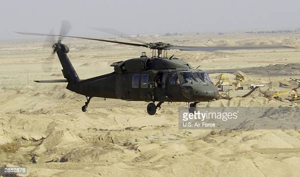 In this US Air Force handout UH60L Blackhawk Helicopter flies a low level mission January 7 2004 in Iraq
