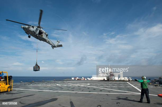 In this US Navy handout An MH60S Sea Hawk helicopter attached to the Sea Knights of Helicopter Sea Combat Squadron 22 delivers cargo to the hospital...