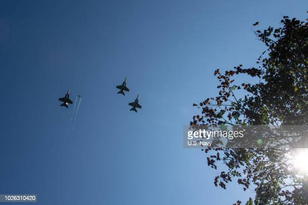 In this US Navy handout F/A18 Super Hornets from Strike Fighter Squadrons 31 VFA32 VFA87 and VFA105 honor the late Sen John McCain with a flyover of...