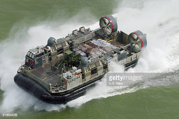 In this US Navy handout photo a Landing Craft Air Cushion vehicle is seen en route to deliver much needed materials and supplies to the citizens in...