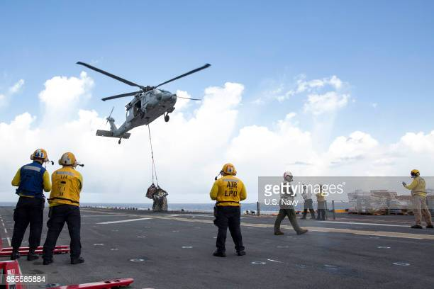In this US Navy handout sailors aboard the amphibious assault ship USS Kearsarge observe as an MH60 Sea Hawk helicopter drops pallets of supplies...