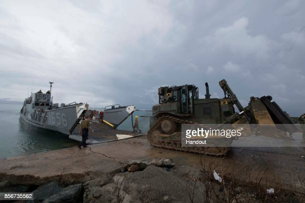 In this US Navy handout sailors offload a bulldozer from Landing Craft Utility 1656 assigned to the amphibious dock landing ship USS Oak Hill...