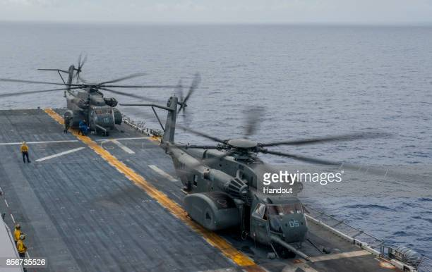 In this US Navy handout Sailors secure two MH53E Sea Dragon helicopters assigned to the 'Blackhawks' of Helicopter Mine Countermeasures Squadron 15...