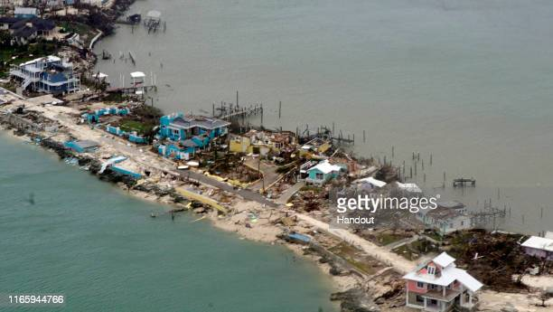 In this USCG handout image, Overhead view of a row of damaged structures in the Bahamas from a Coast Guard Elizabeth City C-130 aircraft after...