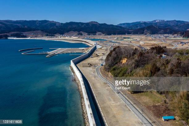 In this view from a drone, a huge, recently-built, concrete tsunami wall runs along the shoreline in Rikuzentakata where 1554 people were killed in...