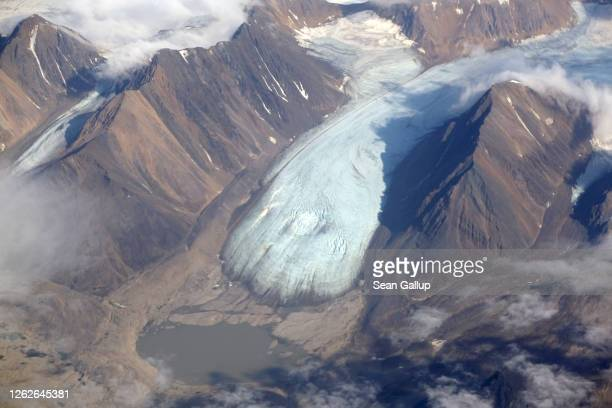 In this view from a passenger plane a melting glacier that shows a depression due to meltwater flowing underneath is seen during a summer heat wave...