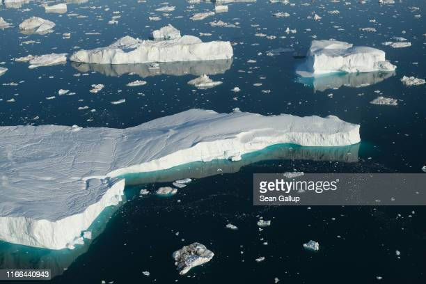 In this view from an airplane icebergs float at the mouth of the Ilulissat Icefjord on August 04, 2019 near Ilulissat, Greenland. The Sahara heat...