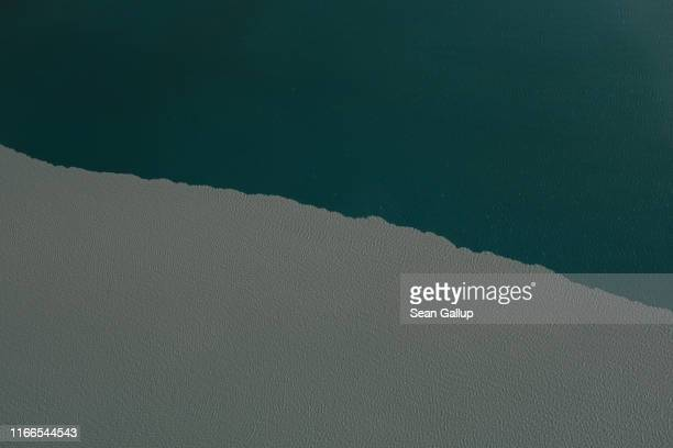 In this view from an airplane silty meltwater coming from the Greenland ice sheet meets clean water in a lake near the Sermeq Avangnardleq glacier on...
