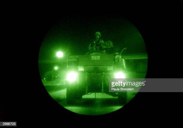 In this view through a night vision scope a soldier with the US Army 1st Armored Division Brigade Reconnaissance Troop rides atop his vehicle during...