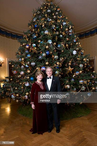 In this White House handout US President George W Bush and first lady Laura Bush pose in front of the Christmas tree in the Blue Room of the White...