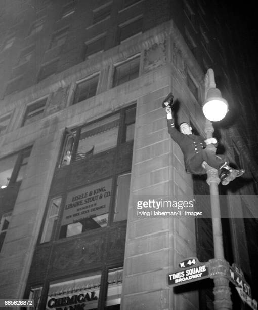 In Times Square a police officer waves his cap from atop a street lamp pole as he celebrates VE Day New York New York April 12 1945