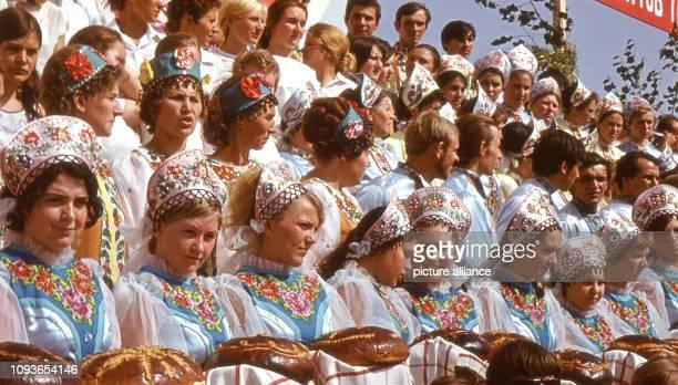 In traditionelle russische Trachten gekleidete Mitglieder eines Laienchores, von denen einige Brot und Salz darbieten, sind bereit, während eines...