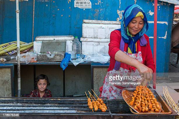 CONTENT] In Turpan Bazaar a lady cooks kebabs while her daughter watches the scene from under a table