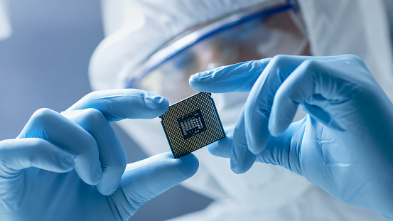 In Ultra Modern Electronic Manufacturing Factory Design Engineer in Sterile Coverall Holds Microchip with Gloves and Examines it. 823447826