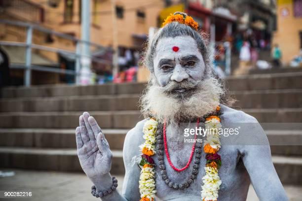 In Varanasi, Indian sadhu greeting people with his hand up.