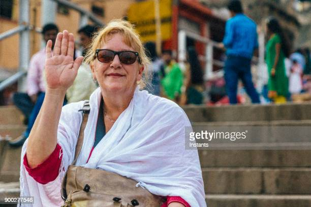in varanasi, senior tourist sitting on one of the ghat stairs. - ghat stock pictures, royalty-free photos & images