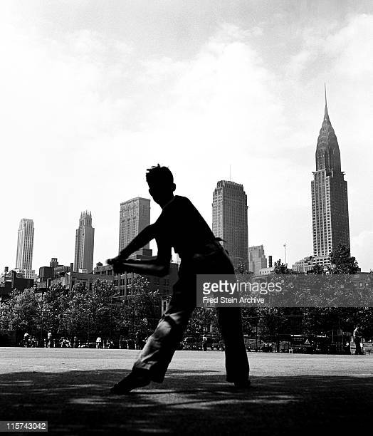 In view of the Chrysler Building a boy swings a baseball bat in a public park New York New York 1946