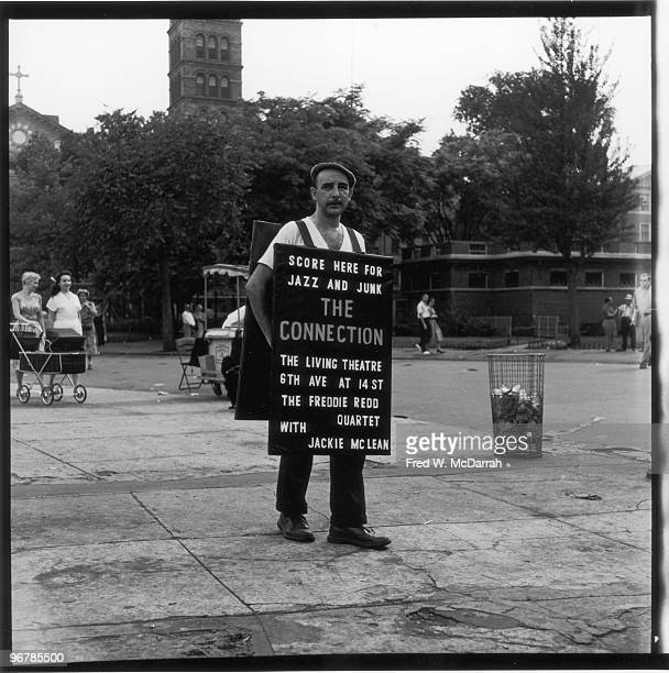 In Washington Square Park an unidentified man wears a sandwich board sign that advertises the Living Theatre's production of Jack Gelber's play 'The...