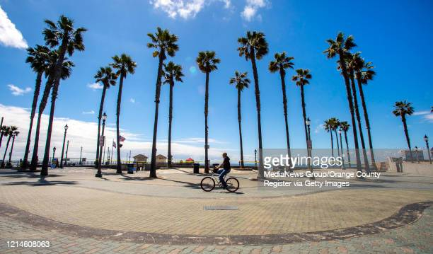 In what would normally be a busy spring break at the beach a lone cyclists rides past the palm trees near the Huntington Beach Pier which is now...