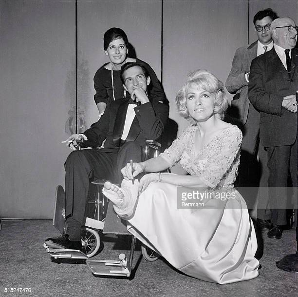 Ina Balin pushes wheelchair and Ben Gazzara who fractured his left leg Julie Newmar stoops to autograph the cast on his foot Scene is at the Astor...