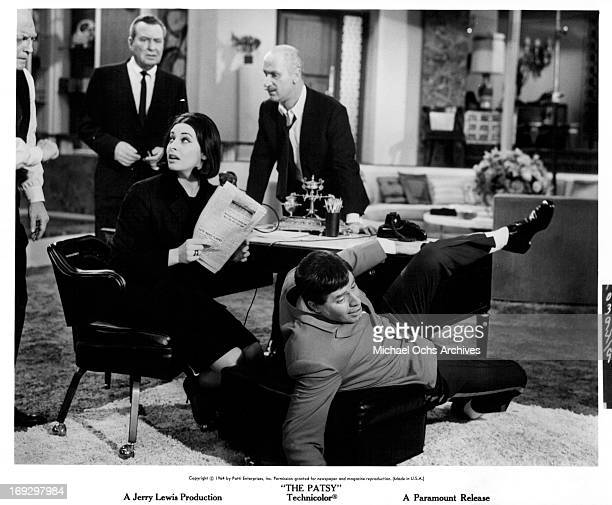 Ina Balin reads a paper as Jerry Lewis falls over in a scene from the film 'The Patsy' 1964