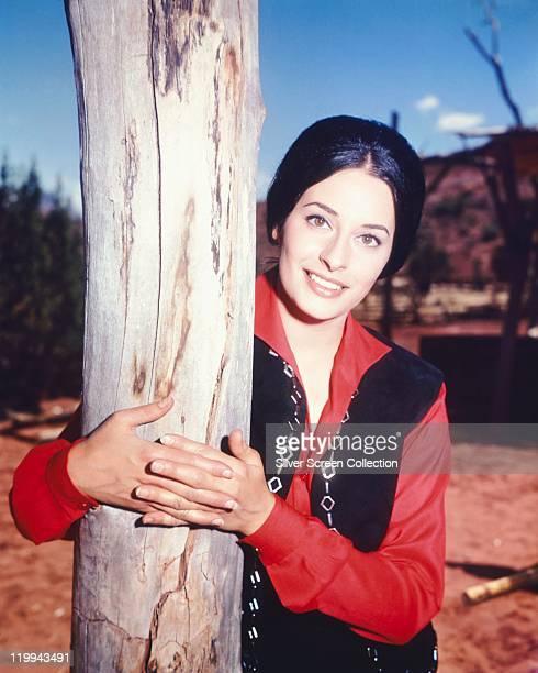 Ina Balin US actress wearing a red blouse beneath a black waistcoat hugging a tree trunk circa 1970