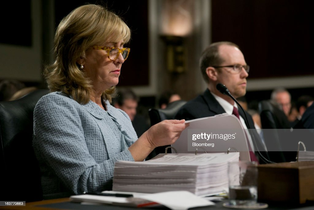 Ina Drew, former chief investment officer with JPMorgan Chase & Co., left, looks through an exhibits binder during a Senate Permanent Subcommittee on Investigations hearing with Peter 'Pete' Weiland, former head of market risk for the chief investment office at JPMorgan Chase, right, hearing in Washington, D.C., U.S., on Friday, March 15, 2013. JPMorgan Chase, the biggest U.S. bank by assets, compensated chief investment office traders in a way that encouraged risk-taking before the unit amassed losses exceeding $6.2 billion, a Senate committee said. Photographer: Andrew Harrer/Bloomberg via Getty Images