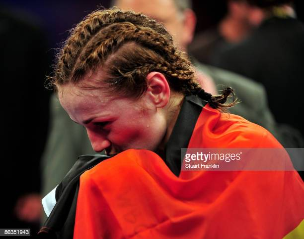 Ina Menzer of Germany kisses the German flag as she celebrates after winning her fight against Franchesca Alcanter of USA during the WIBF and WBC...