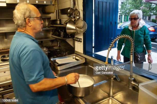 Inaki Berges coowner of the Restaurante Hermandad de Pescadores caters to people who greet him by the window on July 20 2018 in Hondarribia Spain The...