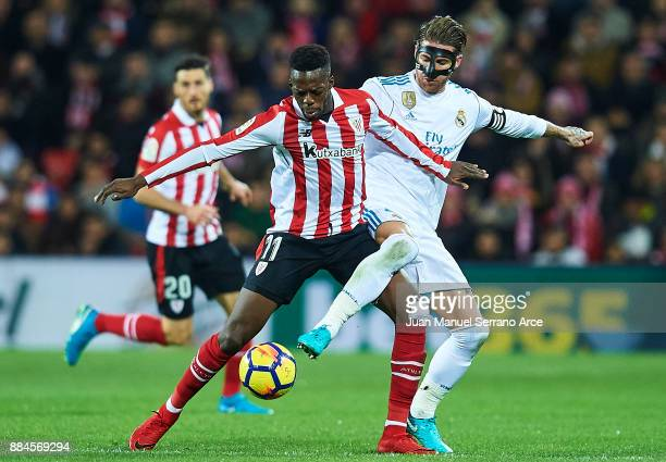 Inaki Williams competes for the ball with Sergio Ramos of Real Madrid CF during the La Liga match between Athletic Club and Real Madrid at Estadio de...