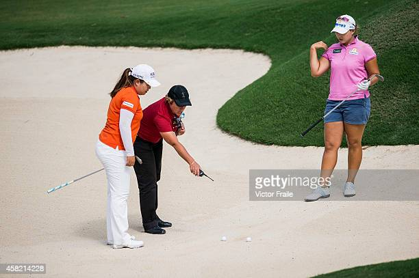 Inbee Park and Mirim Lee discuss with a referee after their balls drops togheter at a bunker on the 8th hole during day three of the Taiwan...