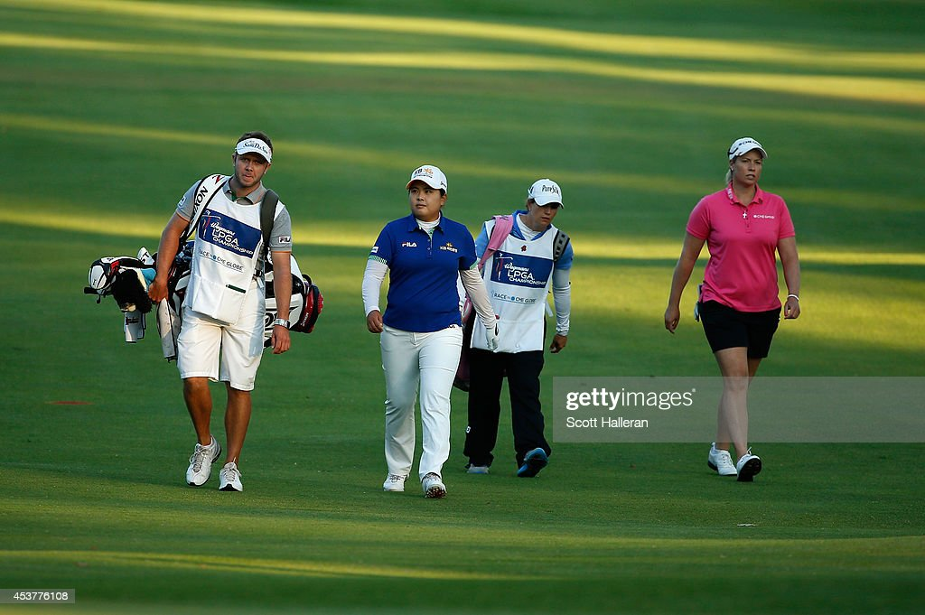 Inbee Park of South Korea and Brittany Lincicome walk with their caddies on the first playoff hole during the Wegmans LPGA Championship at Monroe Golf Club on August 17, 2014 in Pittsford, New York.