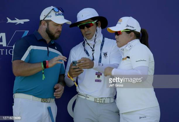 Inbee Park of South Korea and her caddie Brad Beecher look at the phone of Park's husband and coach Gi Hyeob Nam during a practice round prior to the...
