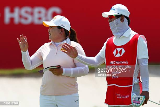 Inbee Park of South Korea and her caddie Gi Hyeob Nam react after completing the first round of the HSBC Women's World Championship at Sentosa Golf...