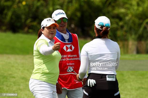 Inbee Park of South Korea and her husband and caddie Gi Hyeob Nam congratulate Xiyu Lin of China after completing the third round of the HSBC Women's...