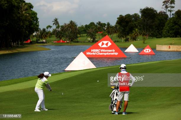 Inbee Park of South Korea plays her second shot from the fifth fairway as her husband and caddie Gi Hyeob Nam looks on during the third round of the...