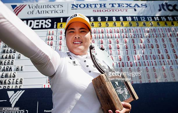 Inbee Park of South Korea pretends to take a selfie while holding the trophy on the 18th green after winning the 2015 Volunteers of America North...