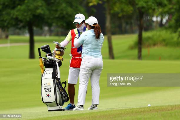 Inbee Park of South Korea puts a towel over her husband and caddie Gi Hyeob Nam as she waits to play her second shot on the 10th fairway during the...