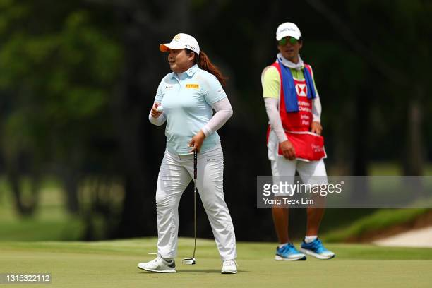 Inbee Park of South Korea reacts after sinking her putt as her husband and caddie Gi Hyeob Nam looks on during the second round of the HSBC Women's...