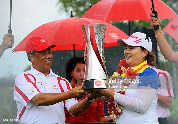 Inbee Park of South Korea receives the Sime Darby LPGA Trophy from the Deputy Prime Minister of Malaysia Tan Sri Muhyiddin Yassin under the rain...